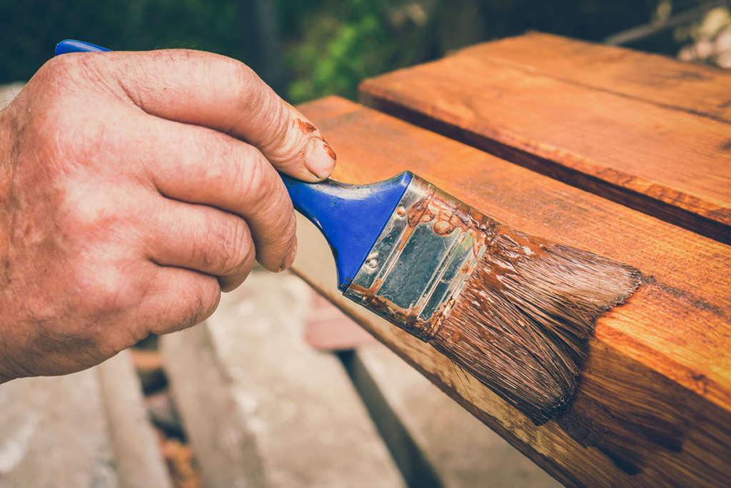 Man staining wood railing